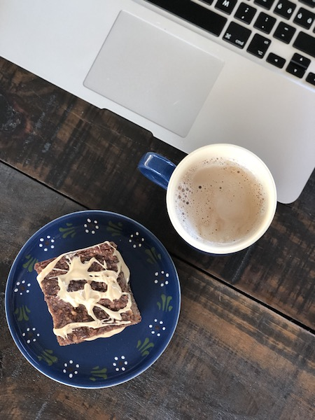 Banana-Bread-Squares on blue plate with coffee and laptop and book on wooden table