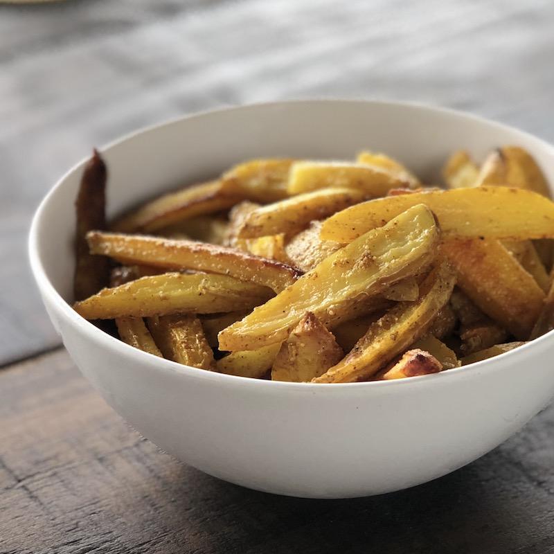 Oven potato fries, vegan, plantbased, in white bowl, on dark brown wooden background