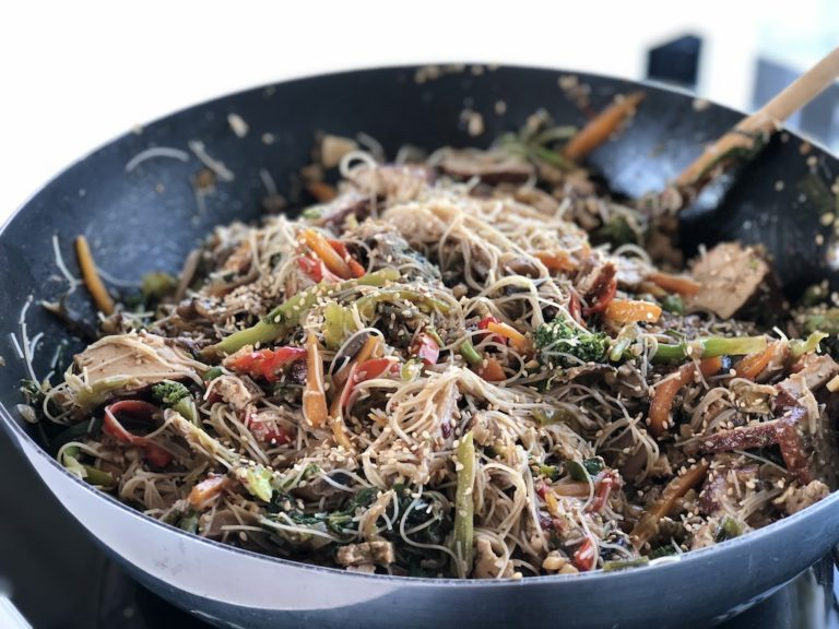 Rice noodles with vegetables and tofu in a wok