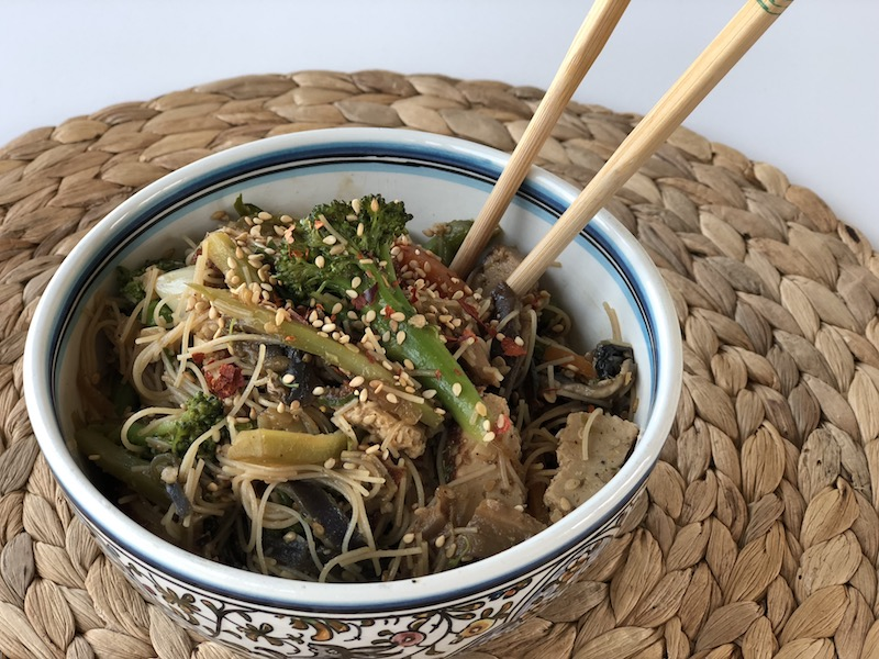 Garlicky Veggie Wok with rice noodles and smoked tofu, vegan, plantbased, in nice ceramic bowl on wooden background with chop stick