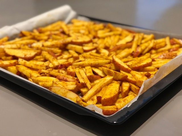 Oven potato fries, vegan, plantbased, before cooking, on baking tray, on grey background