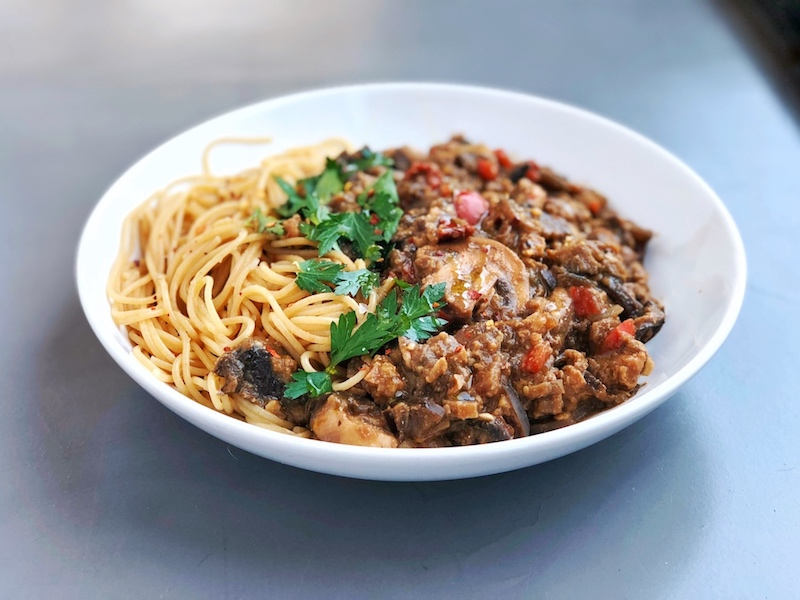 Vegan Smokey Tempeh Eggplant Pasta Sauce with sundried tomatoes plantbased on grey background with parsley