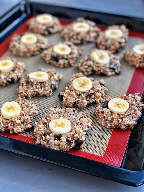 Raw Chocolate-Chip-Banana-Oatmeal-Cookies with Hazelnuts on baking tray
