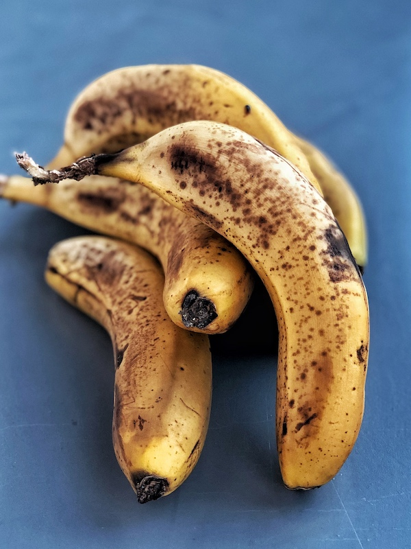 Over-ripe bananas on grey background