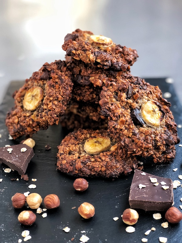 Vegan Chocolate-Chip-Banana-Oatmeal Cookies with Hazelnuts, stacked on black slate