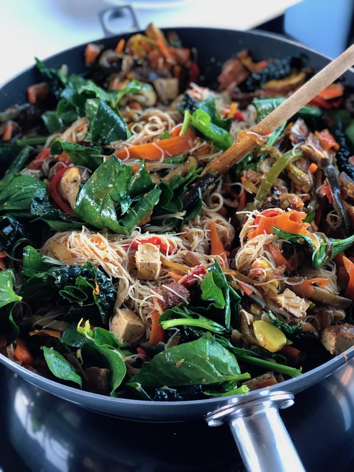 Garlicky Veggie Wok with rice noodles, vegan, plantbased, in wok, white background, tofu