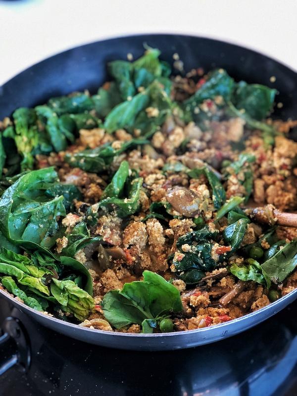 Scrambled tofu with veggies and spinach in a wok
