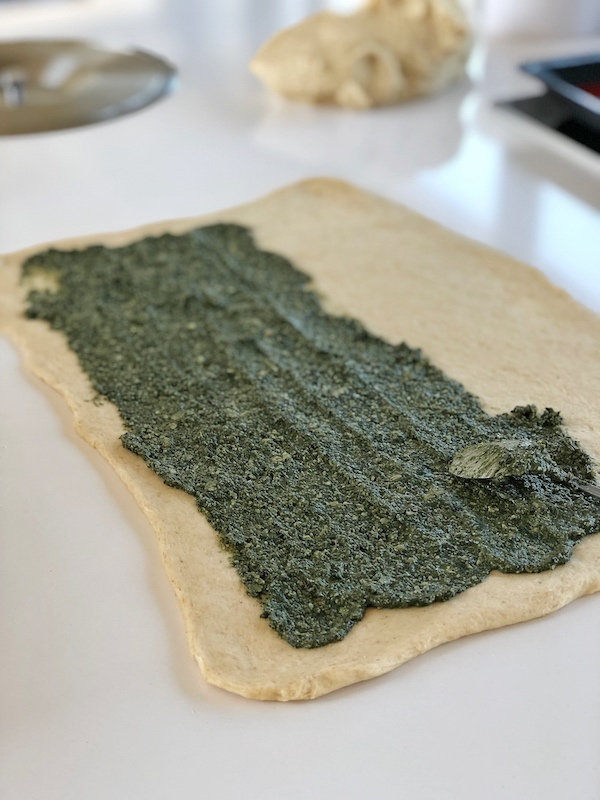 Spreading pesto on dough