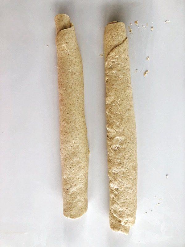 Masa cruda de pan vegano llenado con pesto de albahaca y nueces