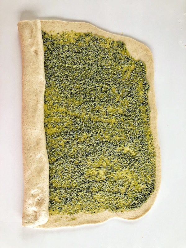 Raw bread dough topped with vegan walnut-basil pesto