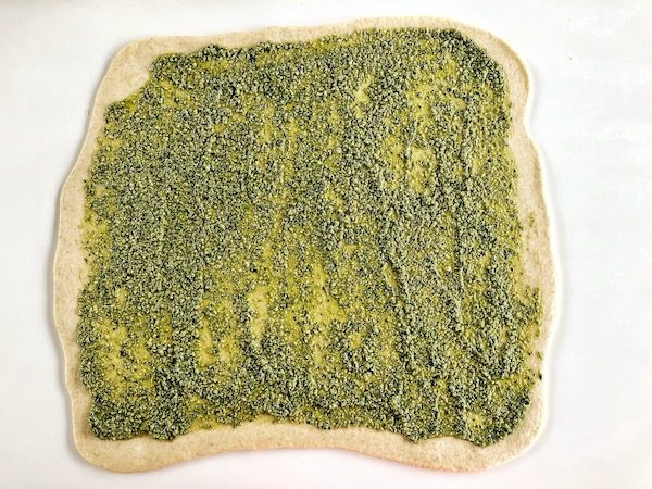 Raw dough of twisted pesto bread, pesto spread on top