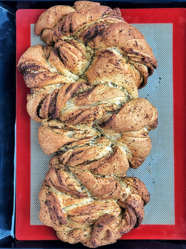 Baked vegan twisted pesto bread on baking tray