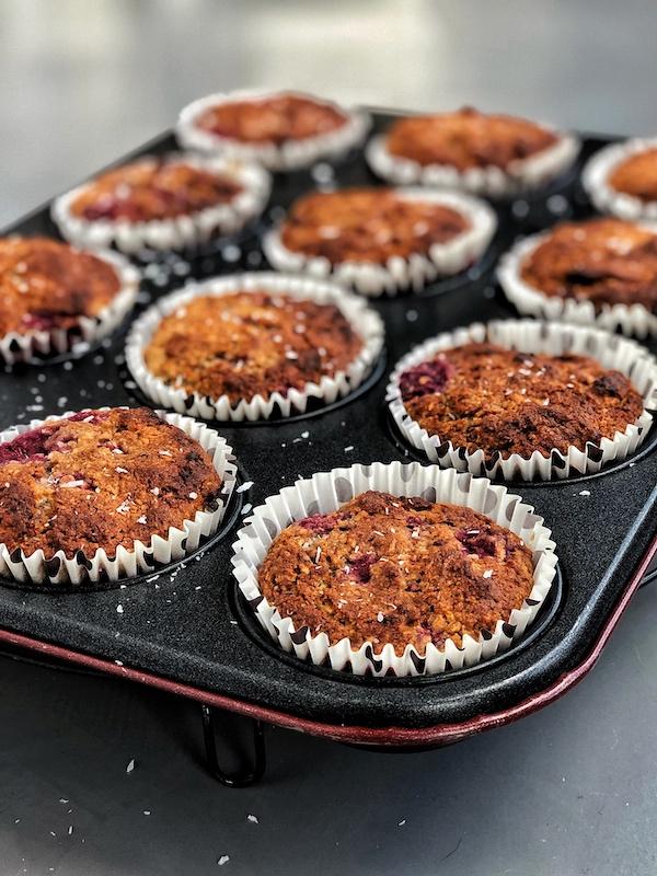 muffins veganos de frambuesa con coco y con un centro cremoso de caramelo de dátiles y anacardos veganos en molde de muffins