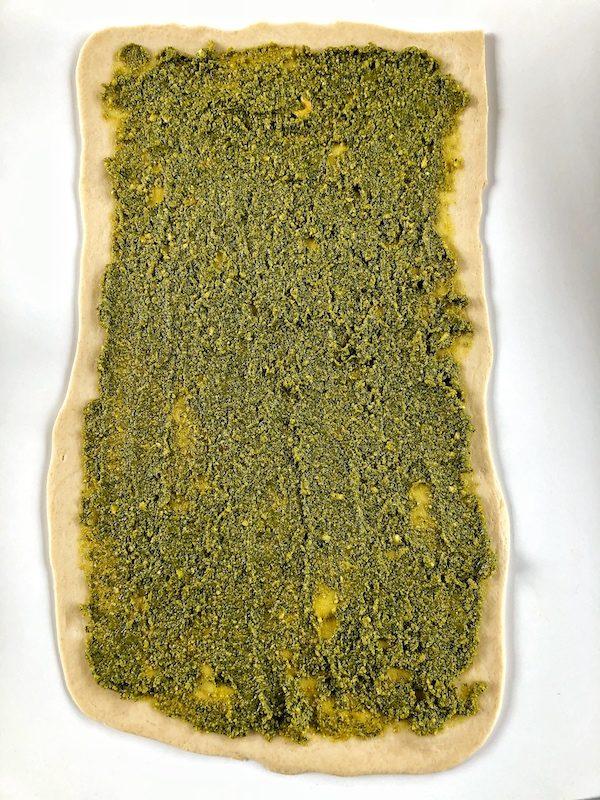Pan trenzado con pesto de anacardos y cúrcuma vegano, masa cruda con pesto encima