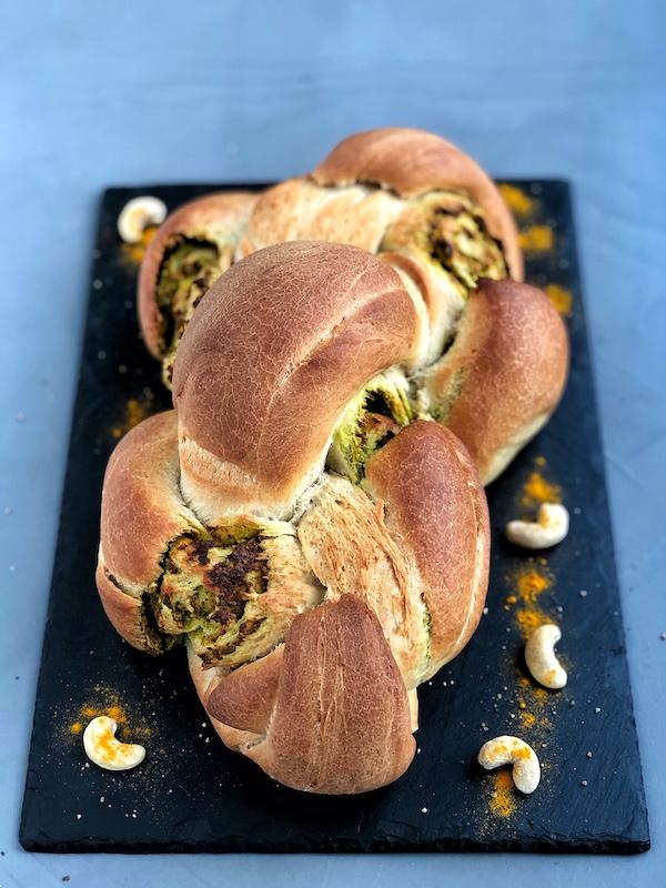Pan trenzado con pesto de anacardos y cúrcuma vegano encima pizarra negra
