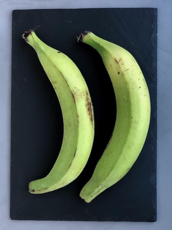 Plátanos verdes (macho) encima de pizarra negra