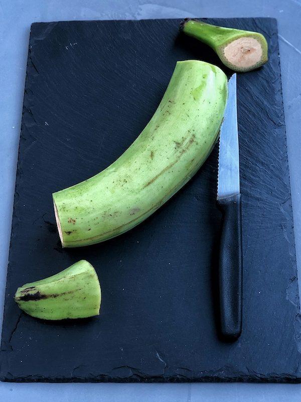 Plátanos verdes (macho) encima de pizarra negra con cuchillo