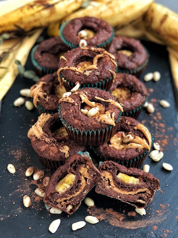 Muffins veganos de Chocolate y Plátano rellenos de Crema de Cacahuete, encima de pizarra negra